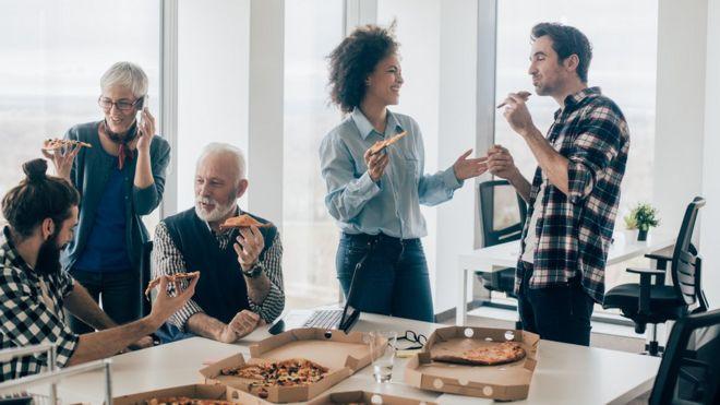 Gente en la oficina comiendo pizza