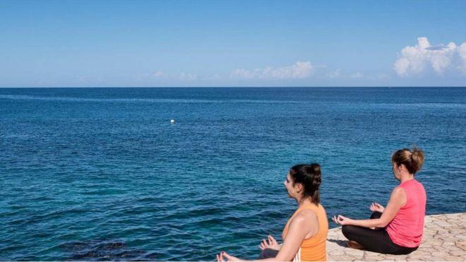 Mulheres meditam em frente ao mar