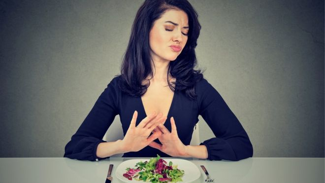 Mujer rechazando un plato de verduras