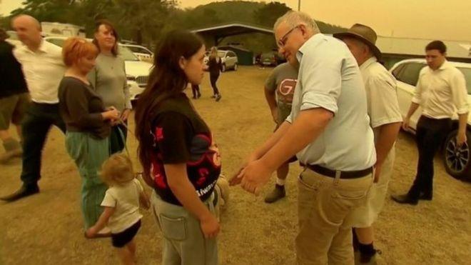 Scott Morrison mova a mão de uma mulher em Cobargo, New South Wales