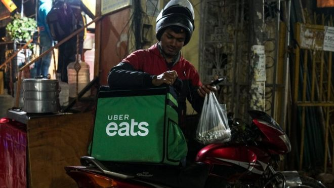 In this photograph taken on February 6, 2019, an Indian delivery man working with the Uber Eats food delivery app loads up food to bring to a customer in New Delhi.