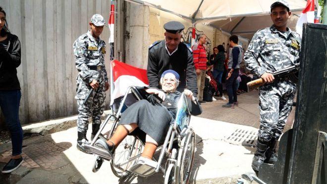 شرطي يدفع كرسي متحرك تجلس عليه امرأة مسنة