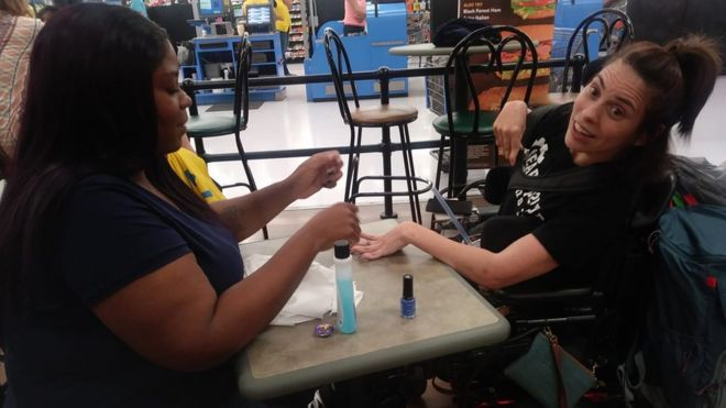 A Picture Of Ebony Harris Painting The Nails Of Angela Peters