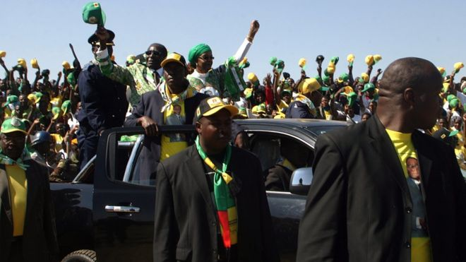 Robert Mugabe (L in car) waves as he arrives to address crowds gathered during an election campaign rally held at Chibuku Stadium, in Chitungwiza on July 16, 2013.
