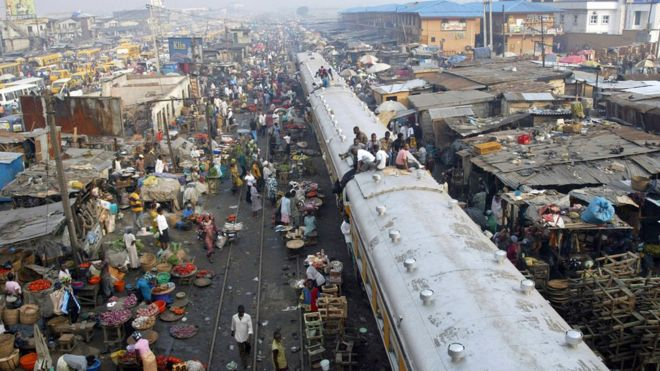 Commuters sitting on top of a train in Lagos, Nigeria.