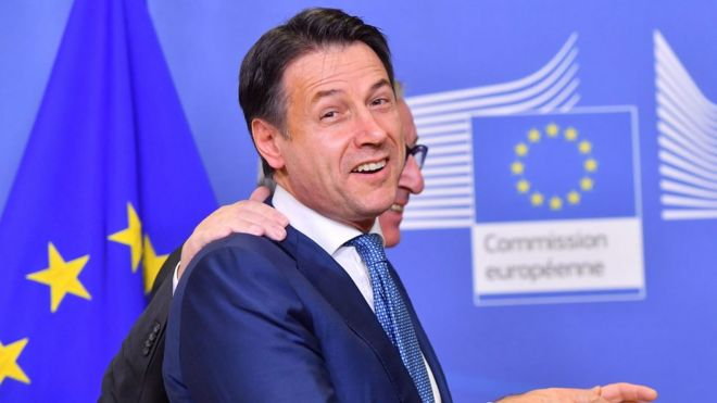Italian prime minister Giuseppe Conte turns to camera, smiling, as he is led away by President of the European commission Jean Claude Juncker