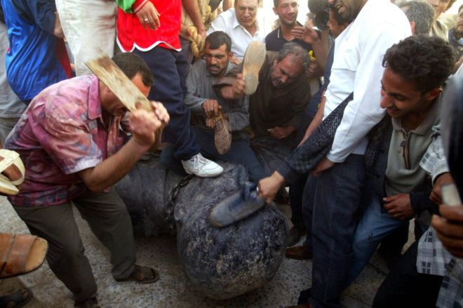 Beating a statue of Saddam Hussein in Baghdad