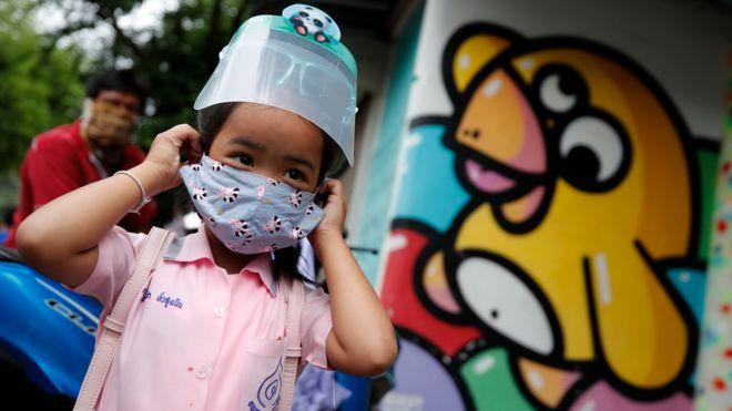 Niña yendo a la escuela en Tailandia con mascarilla.