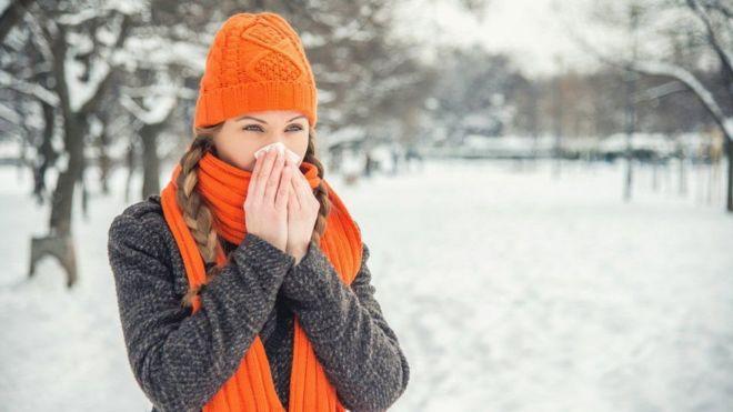 امرأة ترتدي ملابس الشتاء وتحيط أنفها بمنديل