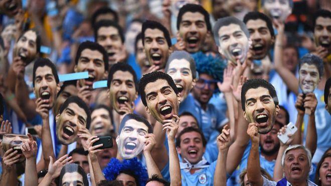 Uruguayos con máscaras de Suárez.