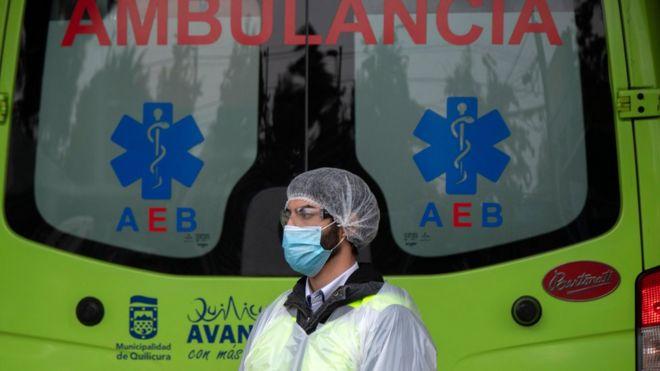 Trabajador sanitario ante una ambulancia en Santiago de Chile