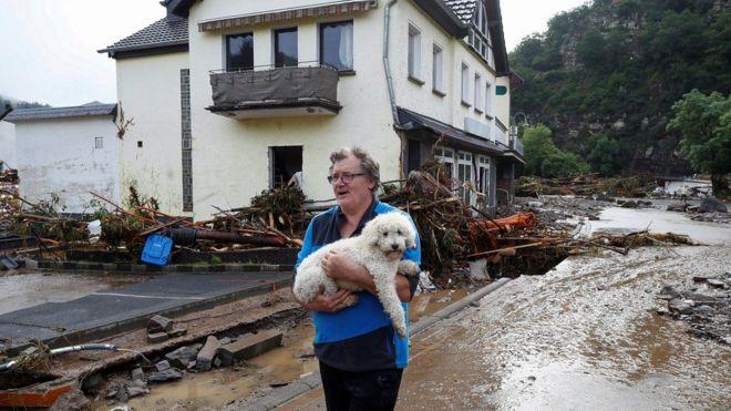 سيدة تحمل كلبها وتحاول الابتعاد عن منزلها المعرض للانهيار