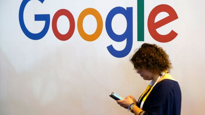 A visitor walks in front of a Google logo during a show at Parc des Expositions in May 2018