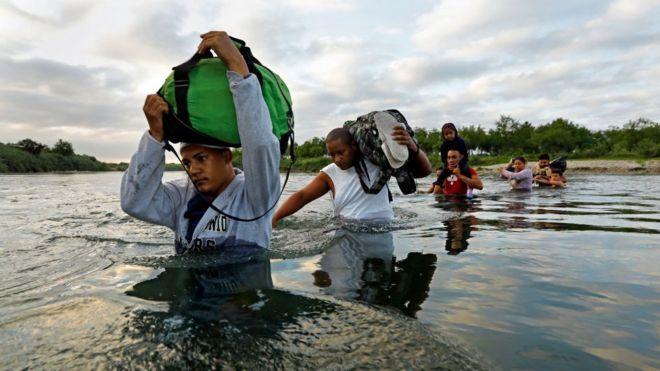 Un grupo de migrantes hondureños y cubanos cruzan el Río Bravo en la frontera entre EE.UU. y México.