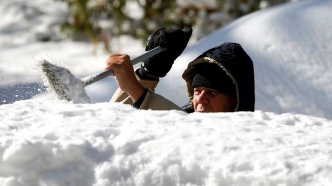 Мужчина убирает снег с верхней части своего автомобиля в Детройте, штат Мичиган, 12 ноября 2019 года.