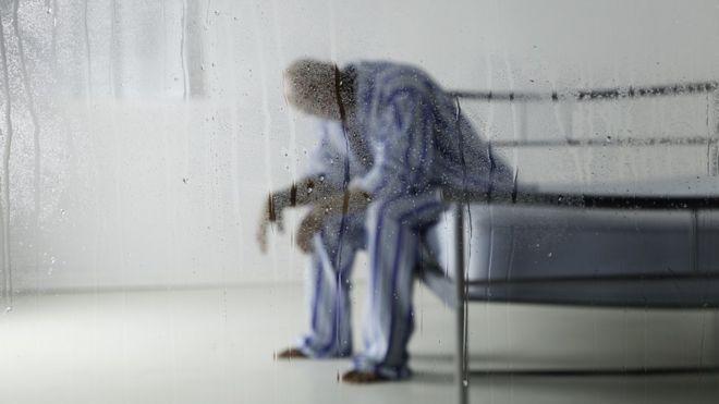 Homem vestido uniforme sentado em cama, atrás de uma parede de vidro