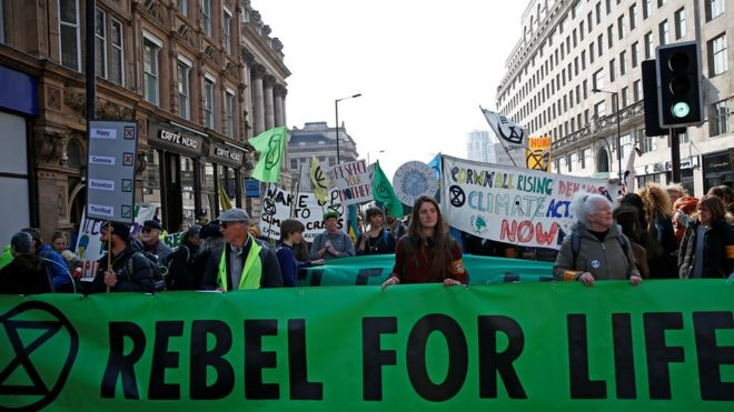"Photo of street protest in London. People holding banners. Main banner reads ""Rebel for Life"""