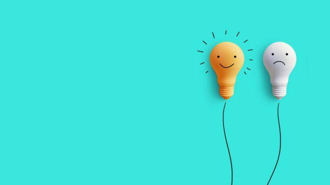 Duas lâmpadas: uma com desenho de carinha feliz e outra triste