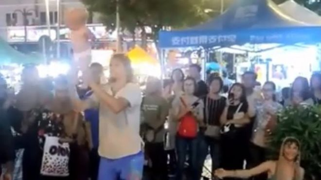 Man swinging baby by the legs