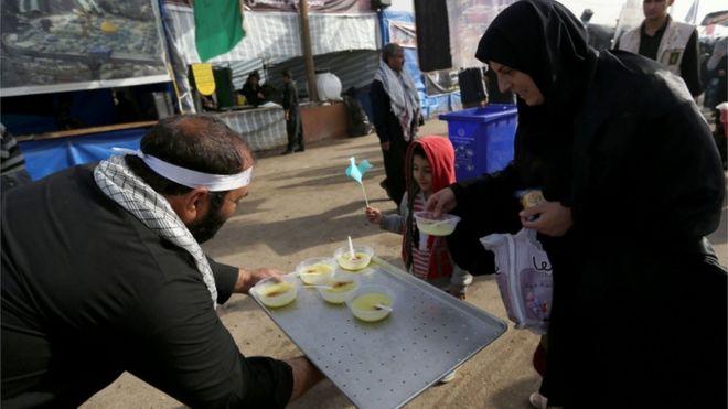 ينتشر على امتداد الطرق متطوعون يقدمون الطعام والشراب مجانا للزوار القادمين سيرا على الأقدام الى المرقد
