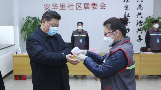 Chinese president Xi Jinping has his temperature recorded during a trip to a hospital in Beijing (10 February)
