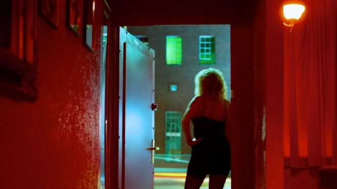 A woman stands at the door of a hotel room