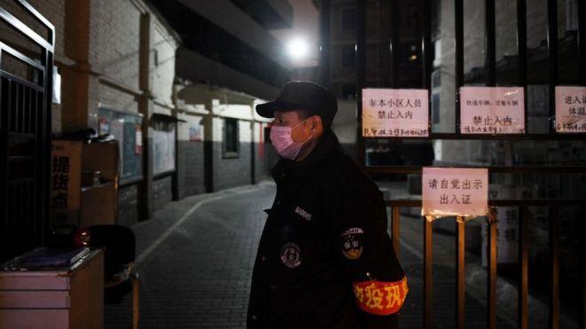 Un guardia a las puertas de un edificio en Pekín.