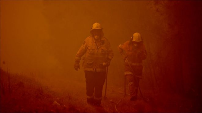 Firefighters tackle a bushfire in thick smoke in the town of Moruya, south of Batemans Bay, in New South Wales on 4 January, 2020.