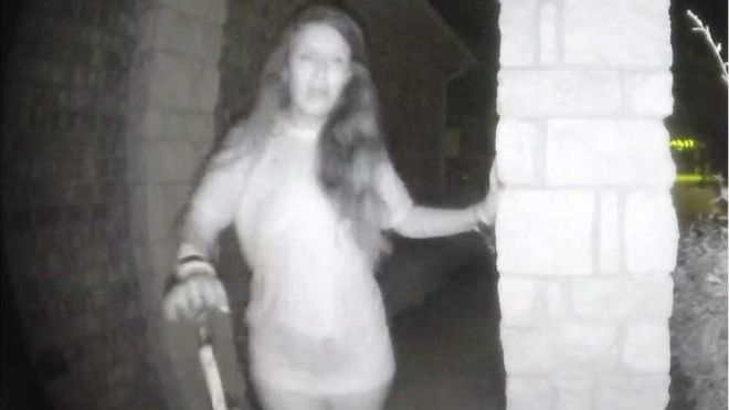 Mulher se aproxima da casa