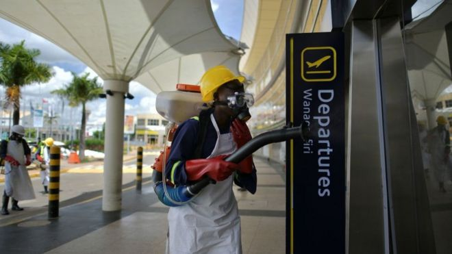 A man spraying disinfectant in an sirport