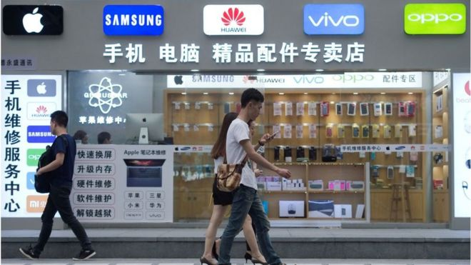 People walking past a phone shop in China