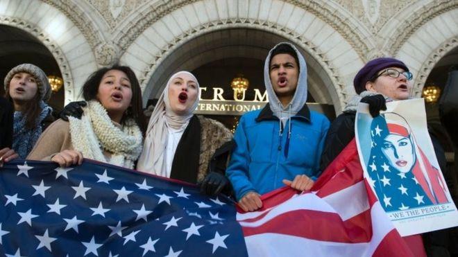 Demonstran memegang bendera AS saat protse di depan Trump Hotel di Washington DC. Foto: 4 Februari 2017