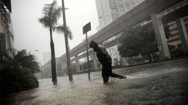 Joven atravesando calles de Miami en medio de la lluvia.