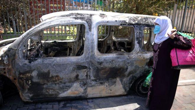 Una mujer pasa frente a un vehículo incendiado en Lod.