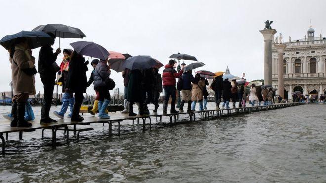 Personas caminan sobre plataformas.