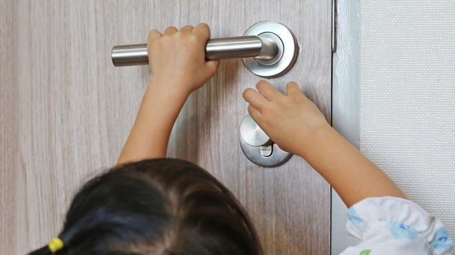 Young Child Trying To Open A Heavy Door