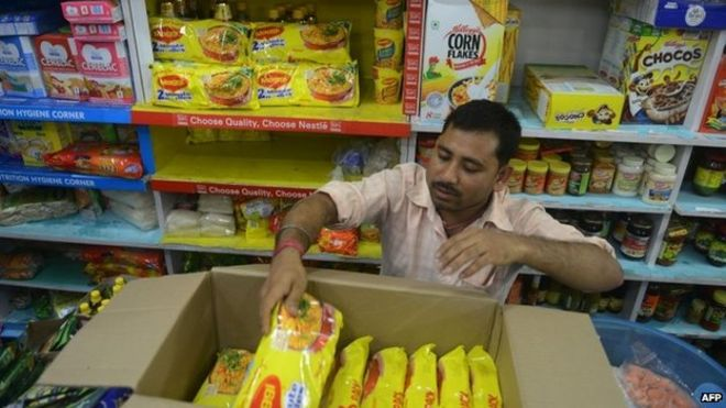 """An Indian shopkeeper removes packets of Nestle """"Maggi"""" instant noodles from the shelves in his shop"""