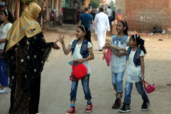 A group of girls is greeted by a woman during the Muslim holiday of Eid al-Fitr, in the village of Dalgamon, Tanta, some 120km north of Cairo, Egypt, 25 June