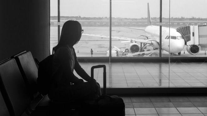 Foto de banco de imagens com jovem segurando uma mala e esperando para embarcar em um saguão de aeroporto, olhando para o avião pela janela