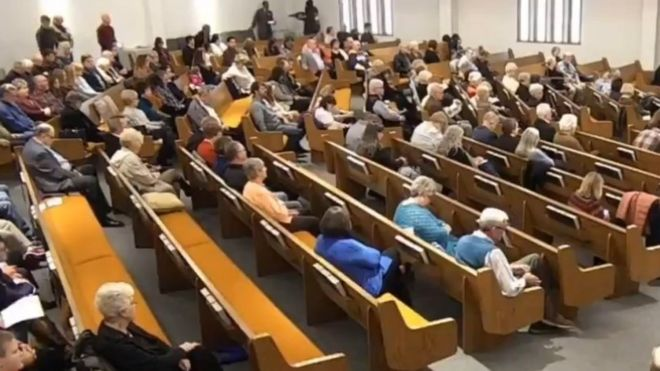 A still from a livestream of the service shows the gunman, in black, seconds after producing a gun, before opening fire