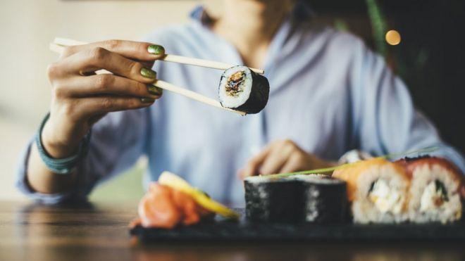 Mujer comiendo sushi.