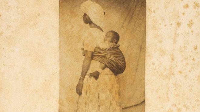 Mulher escravizadas leva o filho preso às costas