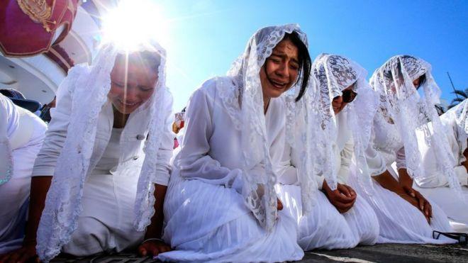 Uma fileira de jovens ajoelhadas chora em uma das Missas da LLDM