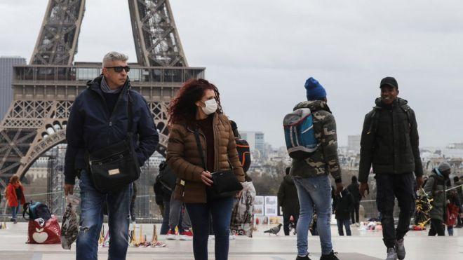 Pessoas em frente à torre eiffel, uma delas usa máscara