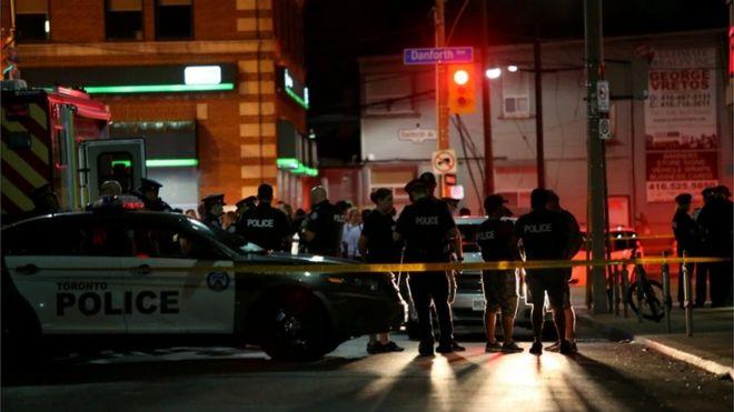 Imagem mostra policiais em área isolada nas proximidades do local onde ocorreu o ataque a tiros em Toronto