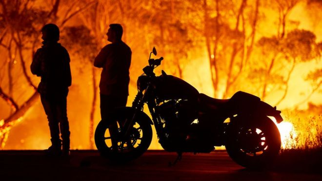Residentes de Lake Tabourie, a unos 200 kilómetros al sur de Sídney, Australia, observan cómo las llamas se devoran un bosque.