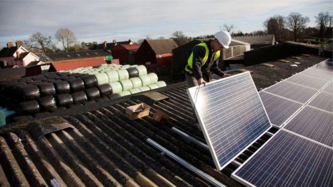 Человек кладет солнечные батареи на крышу