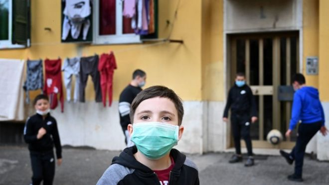 Дети в масках играют в футбол в пригороде Рима