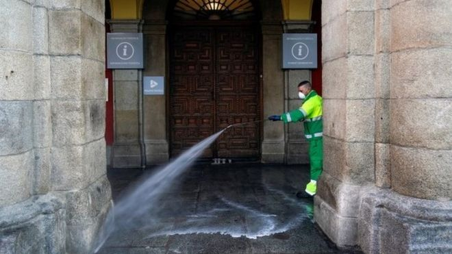 A worker at Madrid city hall hoses down a square
