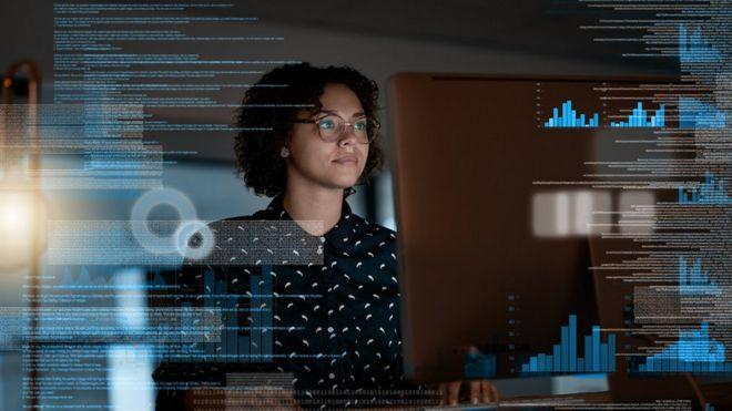 Mulher sentada em frente ao computador, com ilustrações sobrepostas de gráficos